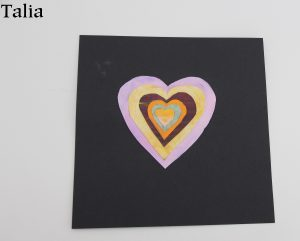 A multicoloured heart on a piece of black backing paper