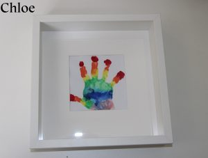 A rainbow painted hand print in a frame