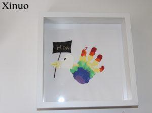 A rainbow handprint shown on a frame to make a bird design